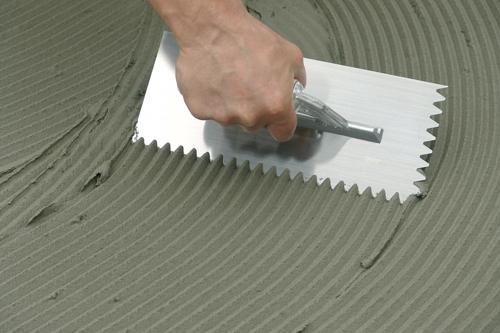 Наносим плиточный клей на пол под кафль
