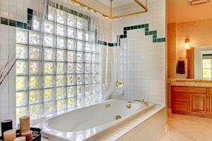 Ванная комната со стеной из стеклоблоков и ванной
